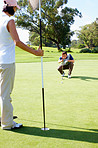 Couple playing golf with man preparing to putt