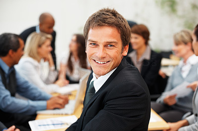 Buy stock photo Successful business man smiling with colleagues having meeting in background
