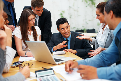 Buy stock photo Colleagues sitting around table near laptop