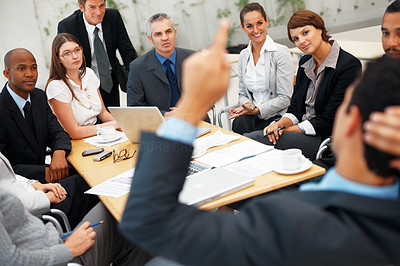 Buy stock photo Focus on colleagues listening to their leader during meeting