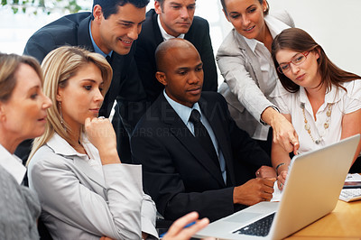Buy stock photo Businesswoman pointing at laptop while colleagues look on