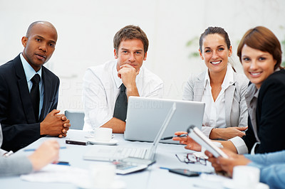 Buy stock photo Executives sitting around a table with laptop computers