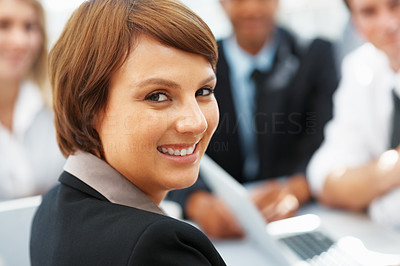 Buy stock photo Closeup of young female executive with colleagues in distance