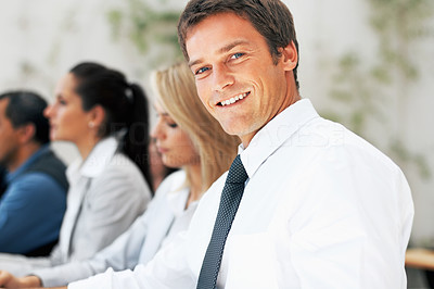 Buy stock photo Closeup of handsome executive with colleagues in distance