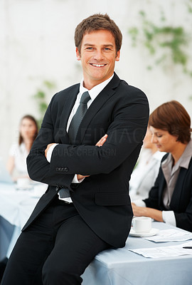 Buy stock photo Portrait of happy business man sitting on a table with colleagues in background
