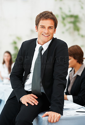 Buy stock photo Portrait of smiling executive sitting on desk with colleagues in background