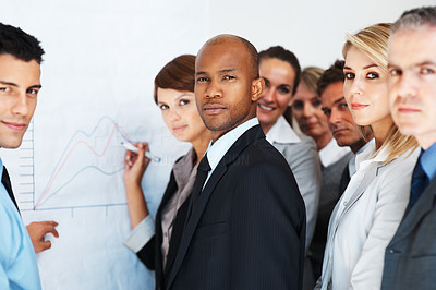 Buy stock photo An african-american businessman standing with his colleagues at a whiteboard