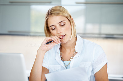 Buy stock photo Portrait of a pretty young woman reading a paper while sitting at her desk in the office