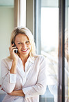 Attractive woman standing by a window using cellphone