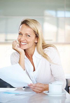 Buy stock photo Portrait of an attractive young businesswoman holding a contract paper and smiling at her desk