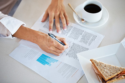 Buy stock photo Cropped image of a woman's hand signing a document with a sandwich and cup of coffee