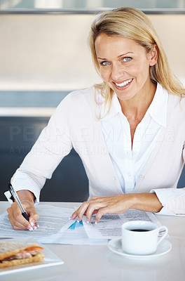 Buy stock photo Portrait of a smiling young businesswoman writing something with with cup of coffee