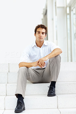 Buy stock photo Portrait of young businessman sitting on stairs of his office