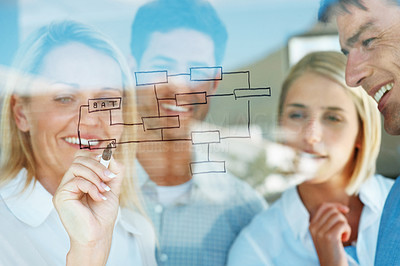 Buy stock photo Successful businesswoman drawing up a presentation with her colleagues