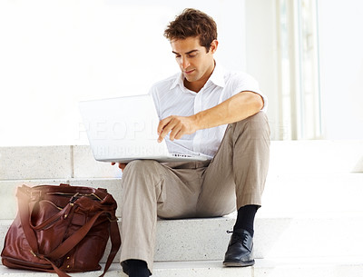 Buy stock photo Smart young businessman using laptop while sitting on steps