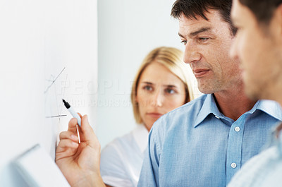 Buy stock photo A smart mature businessman drawing a graph on a whiteboard as his colleagues look on