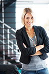 Smiling young businesswoman standing with her hands folded