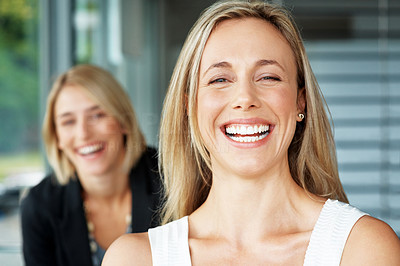 Buy stock photo Pretty young businesswoman laughing with her colleague in background at office
