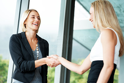 Buy stock photo Successful business colleagues shaking hands with each other at office
