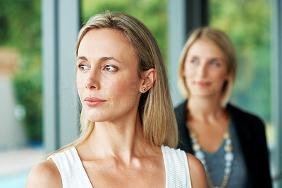 Buy stock photo Portrait of a young businesswoman looking away with woman in background at office