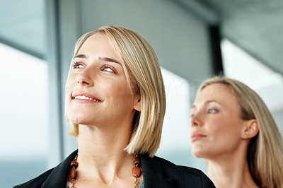 Buy stock photo Portrait of a young businesswoman lost in deep thought with colleague in background - Copyspace