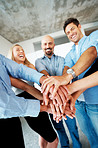 Successful businesspeople stacking their hands together