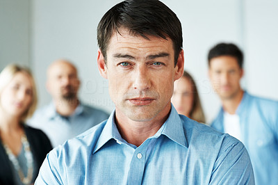 Buy stock photo Confident businessman standing in front with apeople in background