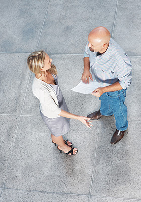 Buy stock photo Top view of two business colleagues standing together and discussing