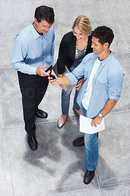 Buy stock photo Top view of happy young man showing a text message to a colleague