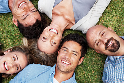 Buy stock photo Portrait of a group of people together lying on grass with a smile