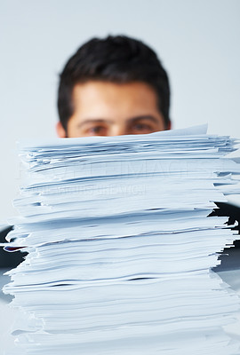 Buy stock photo Focus on stack of paperwork with businessman in background