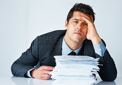Buy stock photo Frustrated businessman with stack of papers on his desk