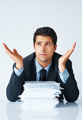 Buy stock photo Overwhelmed businessman sitting with large stack of papers