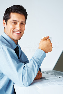 Buy stock photo Happy business man holding cup of coffee in front of laptop