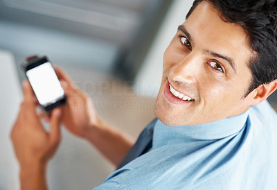 Buy stock photo Top view of man smiling while holding cell phone