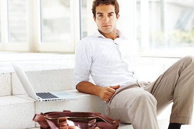 Buy stock photo Portrait of a smart and stylish young man sitting on a staircase with a laptop