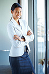 Happy female executive standing casually near window