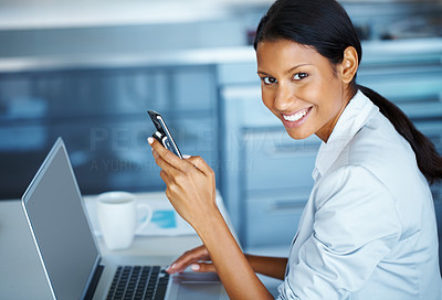 Buy stock photo View of businesswoman holding a cell phone and working on her laptop