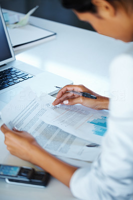 Buy stock photo Side view of business woman looking over papers in front of laptop
