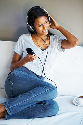 Buy stock photo Pretty woman listening to headphones while sitting on sofa