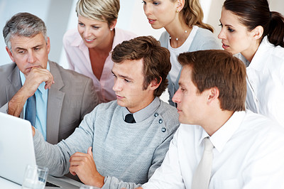 Buy stock photo Group of a business associates working together on laptop at a meeting