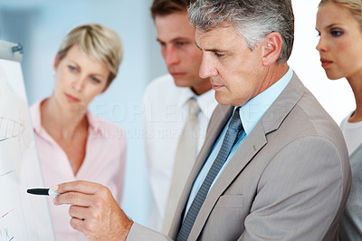 Buy stock photo Mature businessman making a business presentation to a group in boardroom