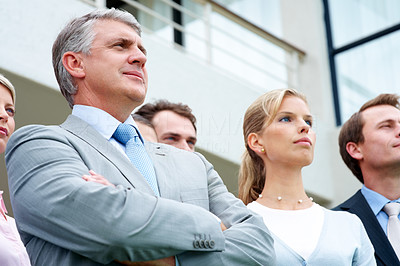 Buy stock photo Senior businessman looking away and thinking for future perspective with his associates in background
