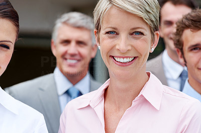 Buy stock photo Beautiful young business woman smiling with associates in background