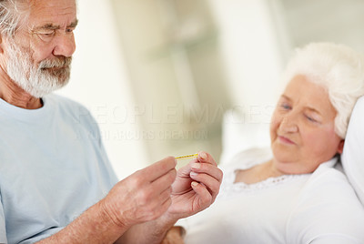 Buy stock photo A senior man reading his wife's temperature on a thermometer while she lies in bed