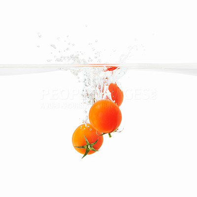 Buy stock photo View of three tomatoes falling into water against white background