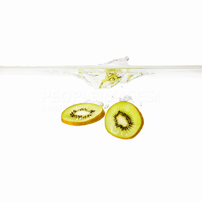 Buy stock photo View of two slices of Kiwi being dropped into water against white background
