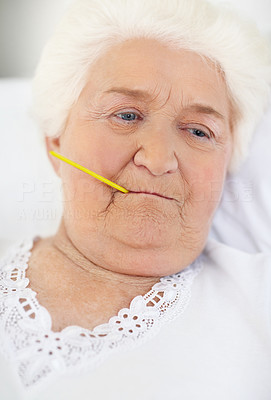 Buy stock photo A senior woman lying in bed with a thermometer in her mouth
