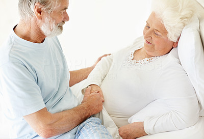 Buy stock photo A senior man caring for and comforting his sick