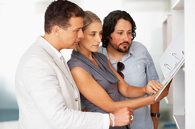 Buy stock photo Three business people reviewing documents at office